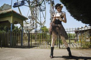 hat young trees girl fence woman ferris wheel pose park grass
