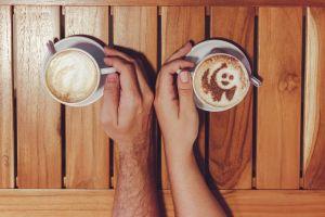 latte art latte man furniture foam wooden coffee caffeine indoors hands