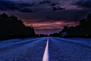 paved road sunset storm