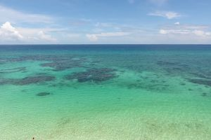 person daylight sea beach water aerial shot beautiful sky man