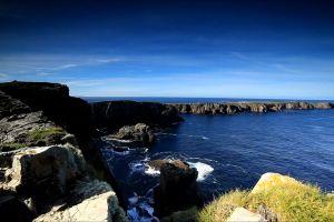 rocks ocean mountain waves cliff beach water rugged sea boulder