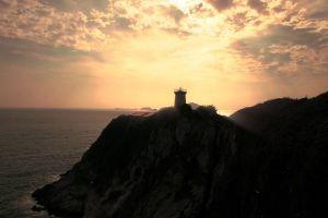 sky beach sunrise ocean lighthouse clouds sea water rocks