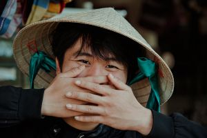 street wear young daylight eyes hands person facial expression straw hat blurred background