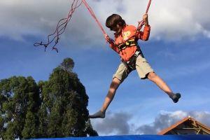 trampoline harness jumping jump sky clouds fun tree kid child