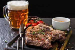 beer food steak cutting board meat tomatoes