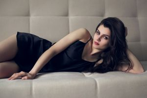 black hair lying down model black dress