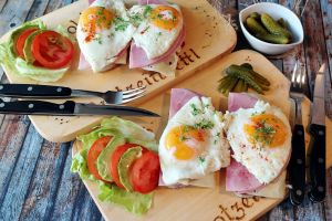 eggs breakfast pickles ham food bread fork lettuce wooden surface cheese cutting board table knife tomatoes