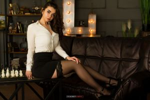miniskirt shirt lights brunette indoors necklace sitting long hair chess women couch stockings women indoors board games heels