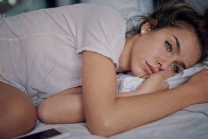 model sad brunette blue eyes ponytail t-shirt long hair women lying on side