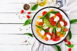 olive oil tomatoes mozzarella wooden surface food basil plates salad black pepper (spice)