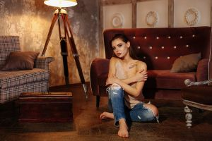on the floor tattoo juicy lips lamp gray eyes barefoot sitting women indoors brunette arms crossed torn jeans women couch