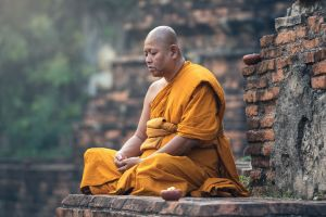 outdoors yellow dress bricks buddhism meditation monastery monks sitting photography bald bald head depth of field closed eyes men
