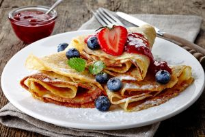 plates blueberries crepes food strawberries wooden surface table knife jam mint leaves sweets fork sugar  fruit