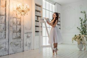 shelf wavy hair skirt ballet slippers flowers chandeliers indoors books ballerina wooden surface model brunette long hair women tiptoe