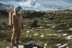 statue astronaut landscape nature mountains wood reflection