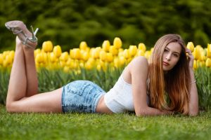 tulips grass brown eyes feet in the air white tops women outdoors high heels lying on front looking at viewer long hair marco squassina legs in the air jean shorts women
