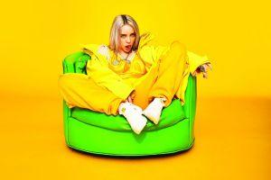 yellow background singer women billie eilish tongue out