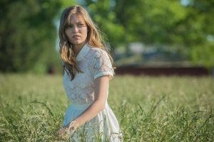 blonde actress looking away white dress field banshee women outdoors see-through blouse