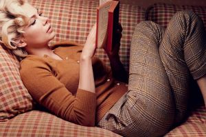 blonde lying down sweater women indoors legs crossed books pants reading actress lying on back couch long hair curly hair women michelle williams