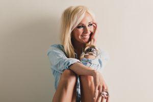 blonde model teeth blue shirt long hair happy looking away simple background women sitting