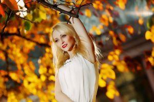 blonde women smiling arms up branch long hair