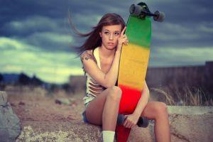brunette sitting jean shorts skateboard looking away long hair tattoo women outdoors women