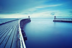 calm waters cyan horizon sea pier blue water calm lighthouse sky