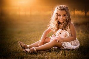 children curly hair sitting stuffed animal grass sunlight