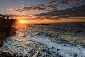 coast clouds rock sunlight sea water sunset waves sky nature lens flare