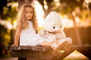 curly hair sunlight bench children bokeh white dress stuffed animal