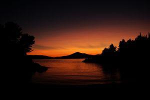 dark water nature calm trees sunset sunlight orange hills