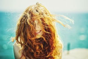 hair in face face women sunlight windy redhead curly hair smiling freckles