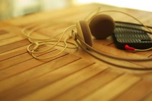 headphones blurred music technology macro wooden surface