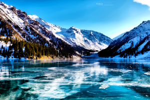 lake nature frozen lake valley snow ice snowy peak trees landscape reflection kazakhstan mountains