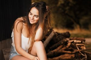 log women long hair smiling shorts white tops jean shorts hands on head
