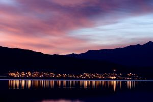 reflection water cityscape pink evening calm waters mountains city lights