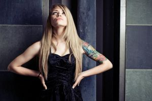 tattoo women looking up hands on hips blonde long hair