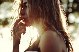 women closeup women outdoors profile finger on lips sunlight blonde