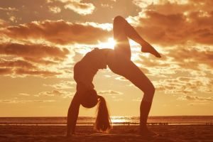 women outdoors sunlight stretching barefoot yoga legs ponytail women clouds sunset beach arched back