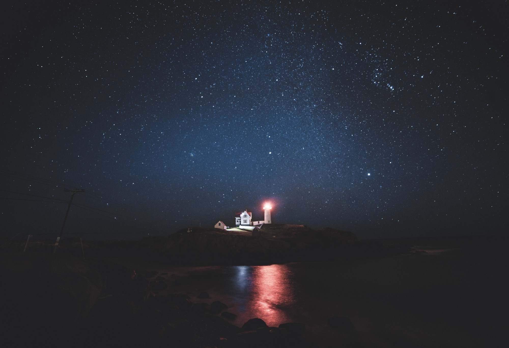 lights dark starry night lighthouse stones sea night reflection stars