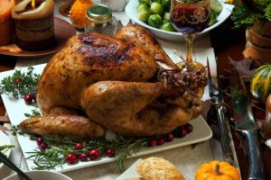 animals flesh food table knife rosemary red wine candles cranberries lemons meat birds death