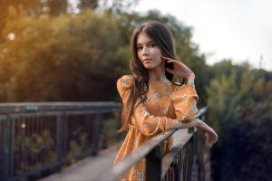 brunette depth of field portrait bridge orange dress model long hair outdoors brown eyes women