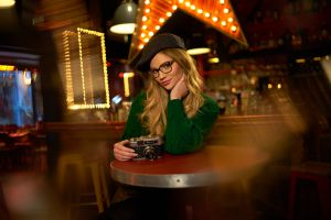 camera women coats photography bar bonnet green clothing portrait looking at viewer women with glasses women indoors sitting sweater bokeh blonde