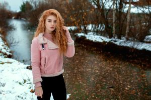 curly hair winter blue eyes redhead portrait standing women trees women outdoors jacket black pants pink sweater snow aleksandr suhar touching hair