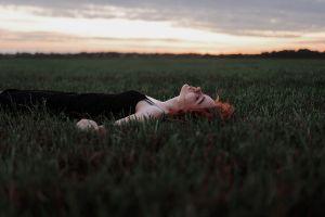 field black dress lying on back portrait pale dress dyed hair grass depth of field outdoors profile bokeh closed eyes model sky