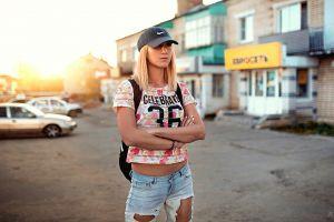 jeans arms crossed painted nails torn jeans outdoors street aleksandr suhar portrait backpacks car nike blonde sun rays depth of field baseball caps