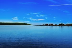 lake clouds landscape blue sky contrail aircraft water village horizon