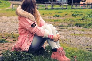 long hair women outdoors looking into the distance pink jacket women model sneakers sitting jeans ombre hair pink shoes women with shades jacket legs together
