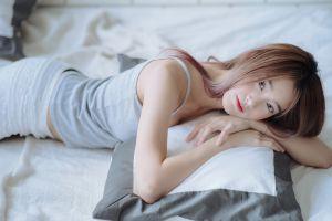 lying on front depth of field pillow looking at viewer grey tops asian model bedroom indoors short shorts in bed women bed women indoors brunette
