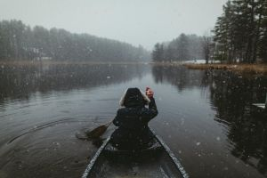 people canoes reflection snowing water plants landscape boat snow trees